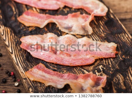 Grilled oily bacon rashers on vintage chopping board close up. Stock photo © DenisMArt