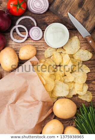 Fresh organic homemade potato crisps chips with sour cream and red onions and spices in paper bag on Stock photo © DenisMArt