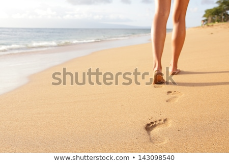 Stockfoto: Woman Walking On Beach Leaving Footprints In The Sand