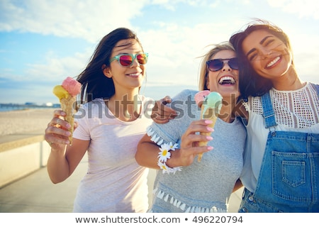 happy friends eating ice cream on beach stock photo © dolgachov