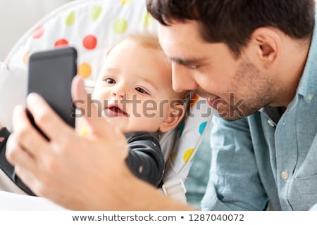 father photographing baby by smartphone stock photo © dolgachov