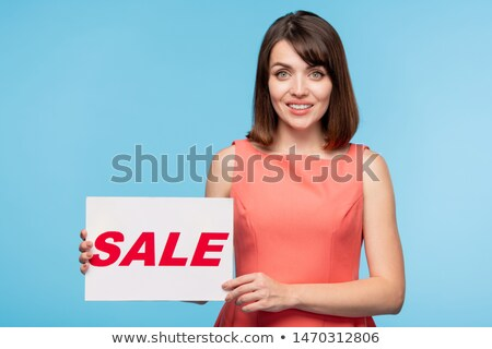 Gorgeous young woman holding paper poster with sale announcement Stock photo © pressmaster