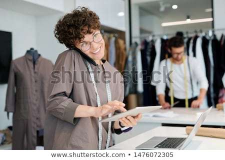 happy female tailor consulting clients or taking orders by phone and online stock photo © pressmaster