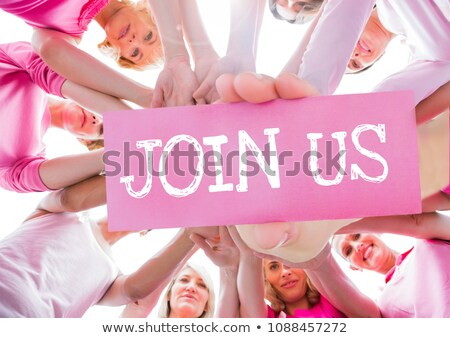 join us text and hand holding card with hands together in circle with pink t shirts stock photo © wavebreak_media