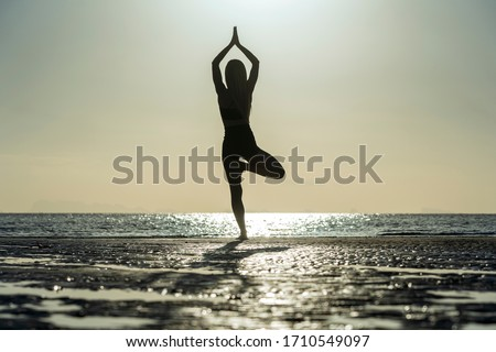 Woman practicing yoga during the sunset stock photo © wavebreak_media