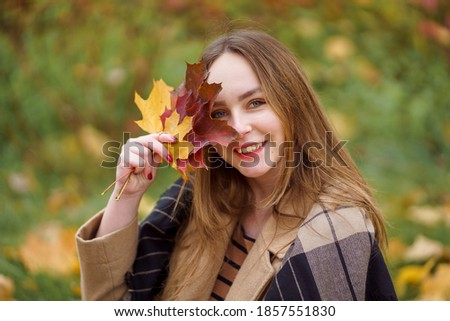 Attractive young girl with a bunch of autumn leaves Stock photo © Nejron