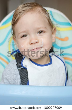 An Adorable baby boy with a mess with cereal on the kitchen Foto stock © Lopolo