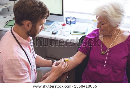 High angle view of confident Caucasian male doctor giving an injection to senior female patient in c Stock photo © wavebreak_media