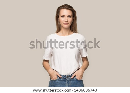 Studio photo of pretty female model stands with crossed arms, has long hair, being confident and sel Stock photo © vkstudio