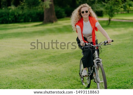 People, nature, rest, lifestyle concept. Happy curly woman rides bicycle among green grass, moves ac Stock photo © vkstudio