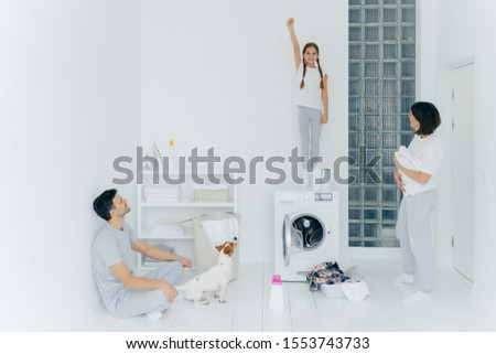 Stock photo: Photo of cheerful girl stands on washing machine, raises arm with clenched fist, helps parents to wa