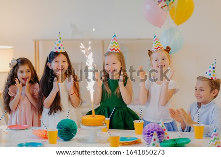 Friends on birthday party, look gladfully at cake, stand near festive table, wear cone hats, clap ha Stock photo © vkstudio