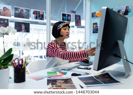 Front view of young mixed-race female graphic designer working on desktop pc at desk in a modern off Stock photo © wavebreak_media