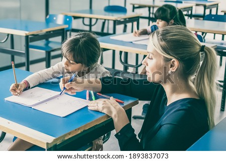 Teacher helping elementary school pupils with their tasks Stock photo © HASLOO