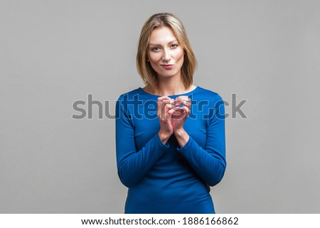 Portrait of a beautiful young businesswoman with hands clasped. Stock photo © HASLOO