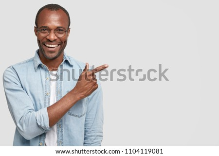 Image of happy african american guy pointing fingers upward at c Stock photo © deandrobot