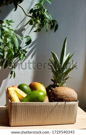 Assortment of organic exotic fruits in box, sunlight. Stock photo © Illia