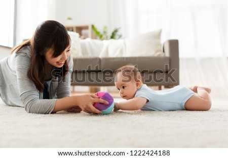 mother and baby playing with ball at home Stock photo © dolgachov