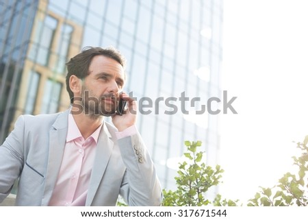 Businessman with mobile phone in front of modern office building Stock photo © Nejron