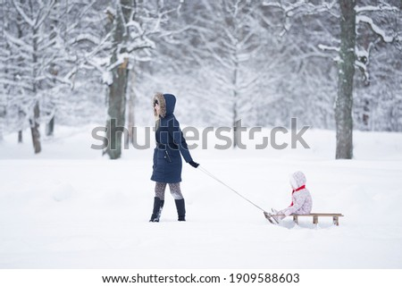 Wintertime Mother with Kid Sitting on Sledges Stock photo © robuart