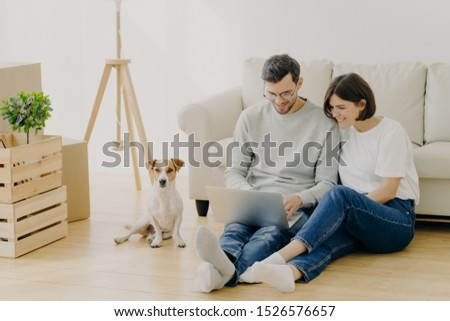 Indoor shot of lovely couple move in new dwelling, use modern laptop for searching design ideas for  Stock photo © vkstudio