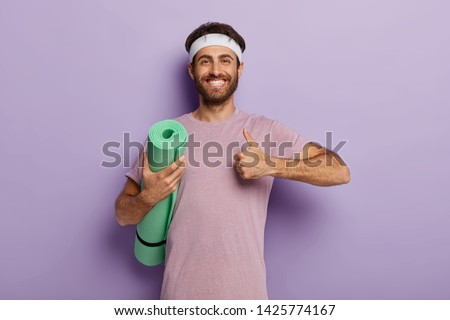 Image of young unshaven man in sportswear posing and looking aside Stock photo © deandrobot