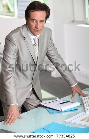 Man in a silver-grey suit purposefully standing by his desk Stock photo © photography33