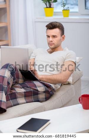 молодым человеком портативного компьютера удобный диване домой компьютер Сток-фото © Lopolo