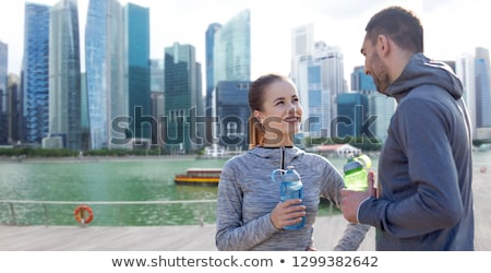 couple with bottles of water over singapore city Stock photo © dolgachov
