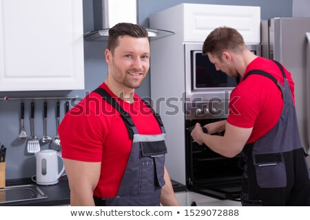 male technician with his assistant repairing the oven stock photo © andreypopov