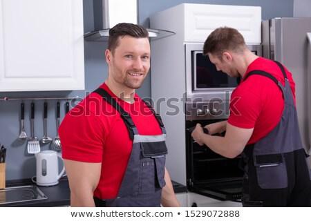 młodych · mężczyzna · pracownika · nowoczesne · piekarnik · kuchnia - zdjęcia stock © andreypopov