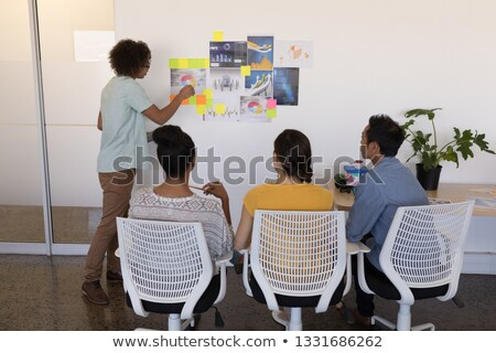 Rear view of mixed race male executive explaining graphs and sticky notes to diverse business team i Stock photo © wavebreak_media