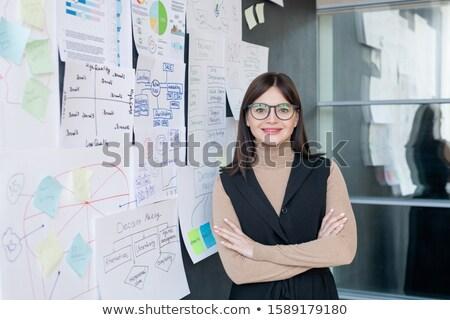 Smiling economist in smart casual and eyeglasses analyzing financial information Stock photo © pressmaster