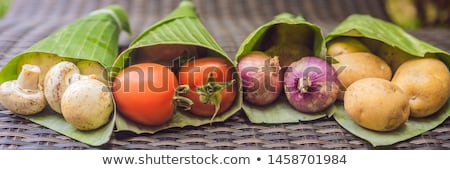 BANNER, LONG FORMAT Eco-friendly product packaging concept. Mushrooms wrapped in a banana leaf, as a Stock photo © galitskaya