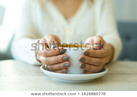 Hands of young restful female holding porcelain cup of fresh hot cappuccino Stock photo © pressmaster