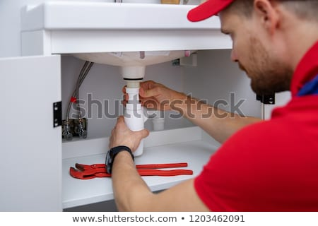Plumber Fixing Sink Pipe And Drain Stock photo © AndreyPopov