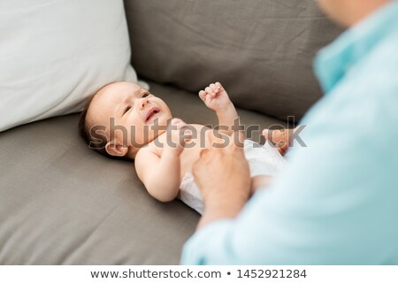 middle aged father changing baby's diaper at home Stock photo © dolgachov