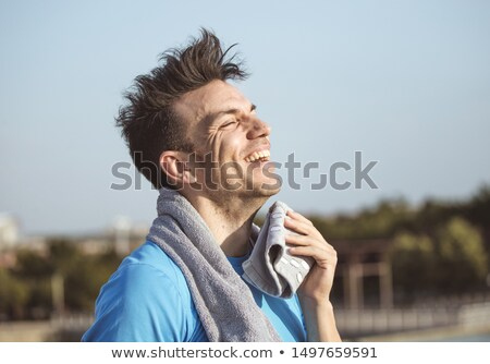 Stock photo: sporty man wiping sweat from forehead after effort