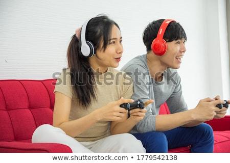 ストックフォト: Woman Listening To Music Through Headphones Boyfriend Watching