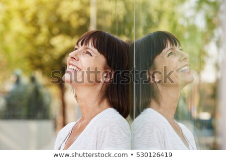 Stock photo: Woman leaning against mirror