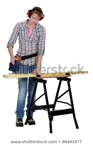 Stock photo: Woman using an electric saw