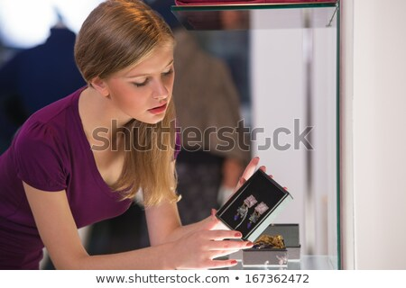 young woman looking at the shop showcase and taking accessories stock photo © hasloo