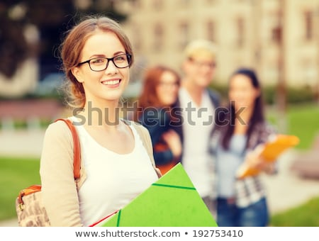 Stok fotoğraf: Female Student In Eyeglasses With Bag And Folders