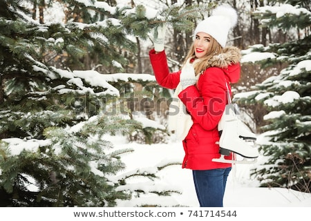 Beautiful smiling blond woman with ice skates stock photo © Kor