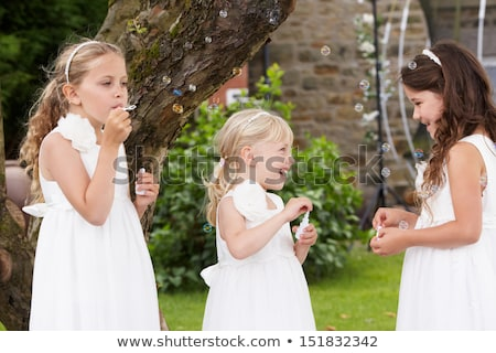 group of bridesmaids blowing bubbles in garden stock photo © monkey_business
