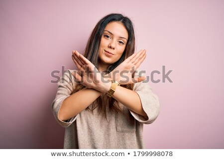 female hands with crucifix over brown background stock photo © tetkoren