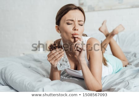 Woman Eating Chocolate In Bed At Home Stock photo © dash c40d85f95