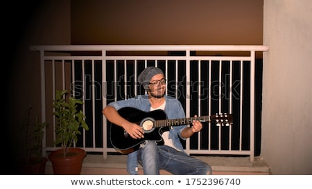 Handsome young male guitarist sitting and playing acoustic guitar Stock photo © deandrobot