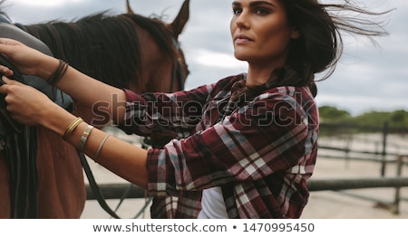 Saddle prepared for horse riding by young woman cowgirl Stock photo © deandrobot