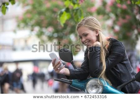 Risonho mulher loira leitura uma boa notícia telefone isolado Foto stock © feedough
